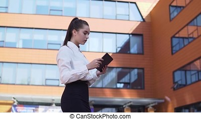 Young business girl walking down the street with a tablet in her hands