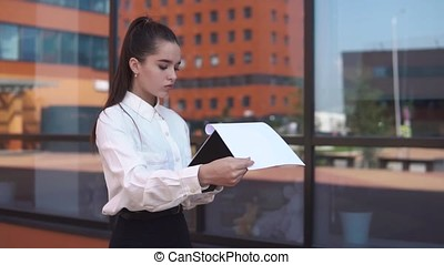 Young business girl walking near business center holding documents in hands