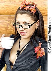 Young business lady in glasses holding a mug with coffee