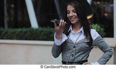 Young business lady using mobile phone near business center. Woman using mobile phone for business communication voice message