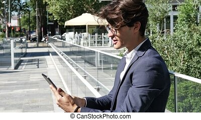 Young business man doing videochat outdoor