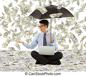 young business man holding a umbrella with dollar rain