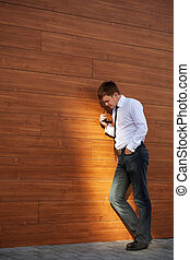 Young business man in depression standing at the wall