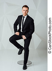 young business man in modern suit sitting on chair - side...