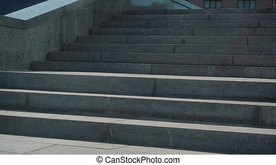 young business man in suit goes down the stairs in the street