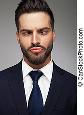 young business man making a stupid face on grey background