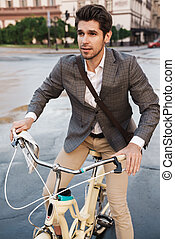 Young business man outdoors on a bicycle