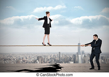 Young business man pulling a tightrope for businesswoman