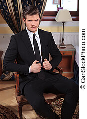 young business man sits on chair