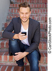 young business man sitting and looking at smart phone