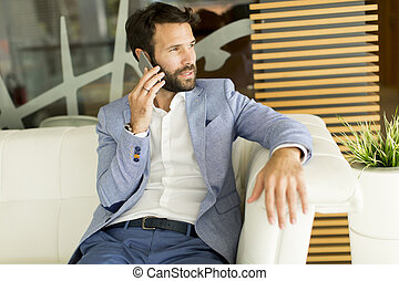 Young business man sitting and using mobile phone