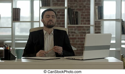 Young business man sitting at office looking up and planning
