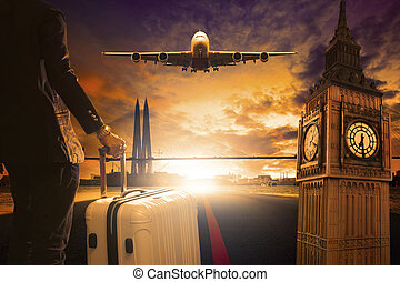 young business man standing with luggage on urban airport runway and jet plane flying above against beautiful urban scen behind