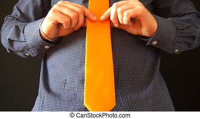 Young business man straightens his orange tie and looks in the mirror at home