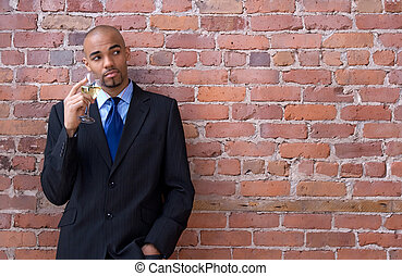 Young business man thinking and holding a glass of wine -...