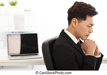 Young business man thinking in the  office