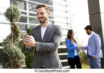 Young business man using a mobile phone outdoor