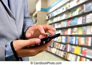 Young Business Man using Mobile Phone in Book store