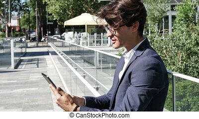 Young business man using tablet computer outdoor