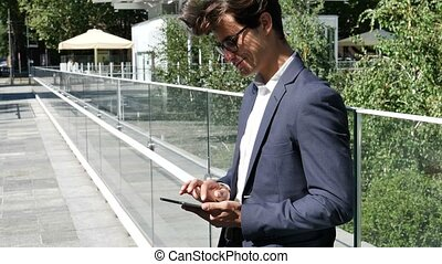 Young business man using tablet PC outdoor