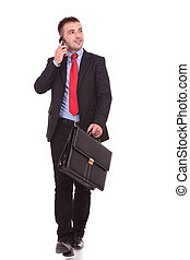 Young business man walking while holding a briefcase