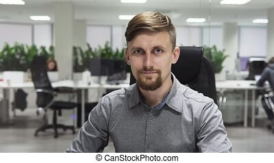 Young business man with a beard smiling at the workplace in office