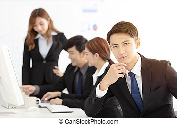 young business man with colleagues on background