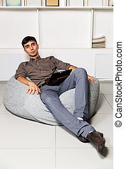 Young business man with tablet computer sitting on a chair