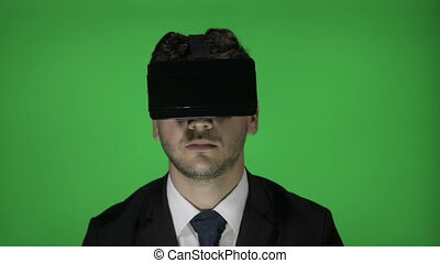 Young business man with virtual reality goggle headset...