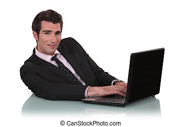 Young business mat sat at desk with laptop
