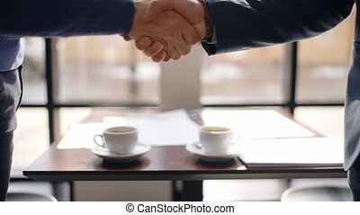 Young business men are shaking hands, say hello, standing at table in restaurant, collaborating people meet for working process, fresh coffee is on desk by window.