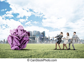 Young business people outdoors and huge paper ball as symbol of creativity