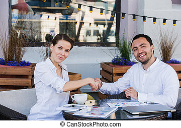Young business people shake their hands in summer cafe