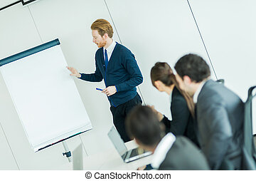 Young business people sitting at a conference table and learning new technologies from the leacturer who is pointing at the whiteboard
