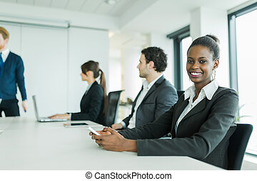 Young business people sitting at a conference table and learning new technologies while having a laugh