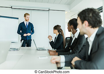 Young business people sitting at a conference table and learning new technologies