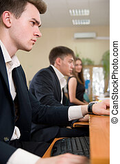 Young business people sitting at a table, using computer