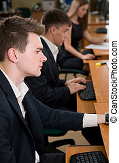 Young business people sitting at a table, using computer when training.