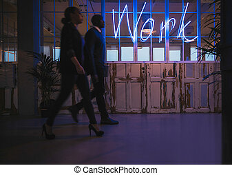 Young business people walking through office corridor