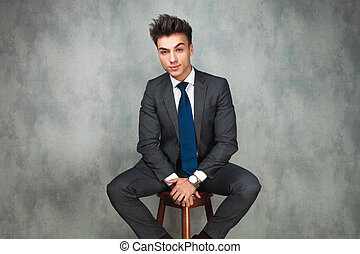 young business resting on a stool