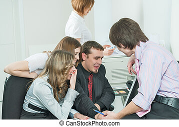 Young business team laugh in front of computer