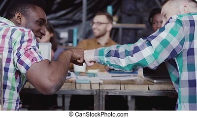 Young business team working together near the table, brainstorming. Two mans fist greeting each other.