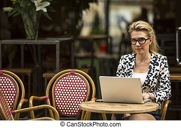 woman at cafe with laptop looking