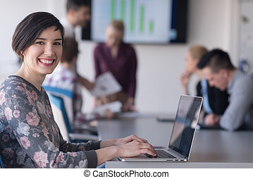 young business woman at office working on laptop with team on meeting in background