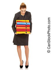 Young business woman carries heavy binders