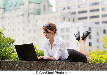 Young business woman casualy works on laptop in the city