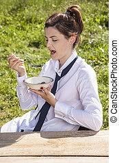 young business woman eats breakfast in the open air