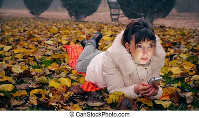 Young business woman gives orders on the phone lying on yellow and red fallen leaves in autumn park.