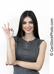 Young business woman giving ok hand sign