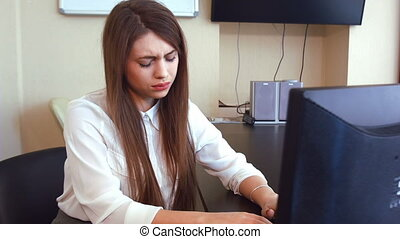 Young business woman has a headache from working at the computer